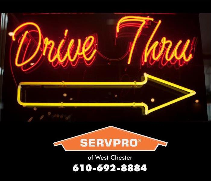 "An orange neon sign reads ""Drive Thru"" and a yellow neon arrow below direct people to the pick-up window of fast food"